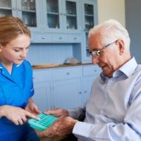 nurse-helping-senior-man-to-organize-medication-on-P2MLAHP